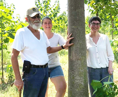 World Tree farmer and team standing next to a beautiful Empress tree.