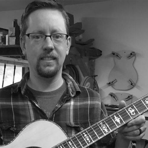 Drew Heinonen holding a guitar made from Empress Lumber.