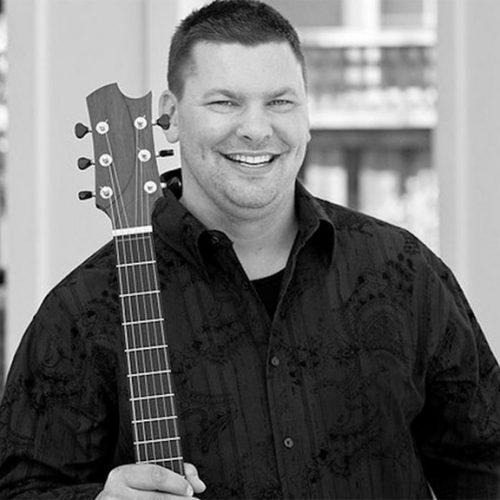 Jason Kostal holding a guitar made from Empress Lumber.